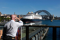 Man looking at Sydney harbour with a cruise ship and Harbour bridge, Sydney, NSW, Australia.
