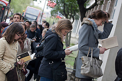 © licensed to London News Pictures. London, UK 06/05/2012. French nationals reading book as they are queueing outside the French Embassy in London to vote the second round of Presidential Elections, this noon (06/05/12). Photo credit: Tolga Akmen/LNP