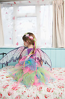 Young girl (5-6) wearing fairy costume sitting on bed by window back view