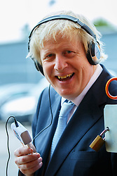 © Licensed to London News Pictures. 14/05/2015. LONDON, UK. The Mayor of London, Boris Johnson giving a radio interview whilst visiting asocial supermarket the Community Shop in Gipsy Hill, south London on Thursday, 14 May 2015 to announce plans to pilot similar schemes across the capital to allow members of the public buy food reduced by up to 70 per cent of normal retail prices by selling surplus products that larger retailers can't use. Photo credit : Tolga Akmen/LNP