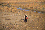 16/12/2015-Chbaish,Iraq-A Ma'dan woman from Chibaish walks on the dry, cracked ground, bringing water from the small stream.