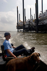 25 Sept, 2005.   Lake Calcasieu, Louisiana.  Hurricane Rita aftermath. <br /> Oil industry rig support platforms prepare to put to sea to repair damaged rigs in the Gulf of Mexico to keep the oil flowing to the U.S. mainland. local man Aaron Stokes and his dog Maggie pass by the platforms.<br /> Photo; &copy;Charlie Varley/varleypix.com