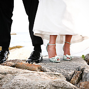 A Bride and Groom show off their feet on the Rocks of the Southport, CT coast.