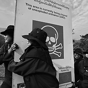 A MAG de-mining team of women removes a roadside sign after clearing an area of uxo - unexploded ordinance - near the Mu Gia pass on Highway 12 near the Vietnamese border in Laos.