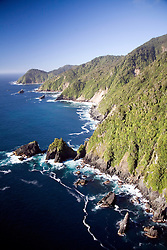 Southland District, New Zealand:  The deep blue of the South Pacific turns to white where it meets the rocky cliffs on the southern tip of the South Island, part of Fiordland National Park.