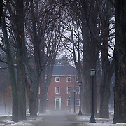 Massachusetts Hall, built in 1802, seen through a stand of trees from the Bowdoin College quad in winter. Fog rises from the melting snow.