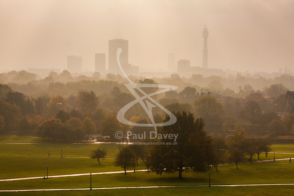 Primrose Hill, London, October 30th. The sun begins to break through as mist shrouds London's skyline, as dog walkers and fitness fanatics enjoy Primrose Hill. Pictured: London's skyline towers over the mist rising at Regent's Park.
