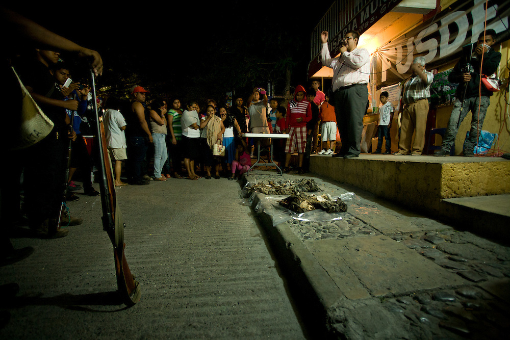Remains of two unidentified people found in the surrounding hills are presented to the people of Petaquillas .