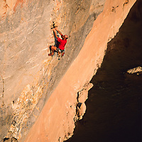 Jose Pereyra makes a bold first ascent from a boat on gear, climbing to the right of ancient rock pictographs, high above the Nam Ou River, Ban Pak Ou, Luang Phrabang, Laos