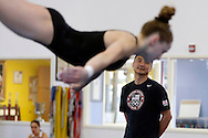 Coach Liang Chow looks on as Rachel Gowey, 18, of Urbandale, goes through her floor routine Friday, June 17, 2016, as Gowey prepares for national competitions and a shot at the Olympic trials at Chow's Gymnastics and Dance in West Des Moines.