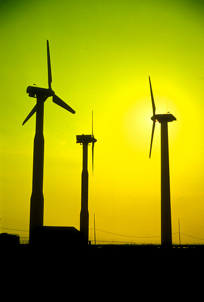 Modern wind turbines silhouetted against green and yellow sky.