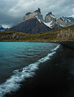 The lapping waves of a turquoise colored lake draw a perfect curve against pitch black sand, with the amazing Cuernos del Paine towering above.