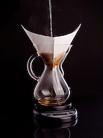 Hot water being poured over ground coffee in a Chemex Coffeemaker to brew coffee. The coffeemaker is sitting on a kitchen scale to measure the exact amount of water added.