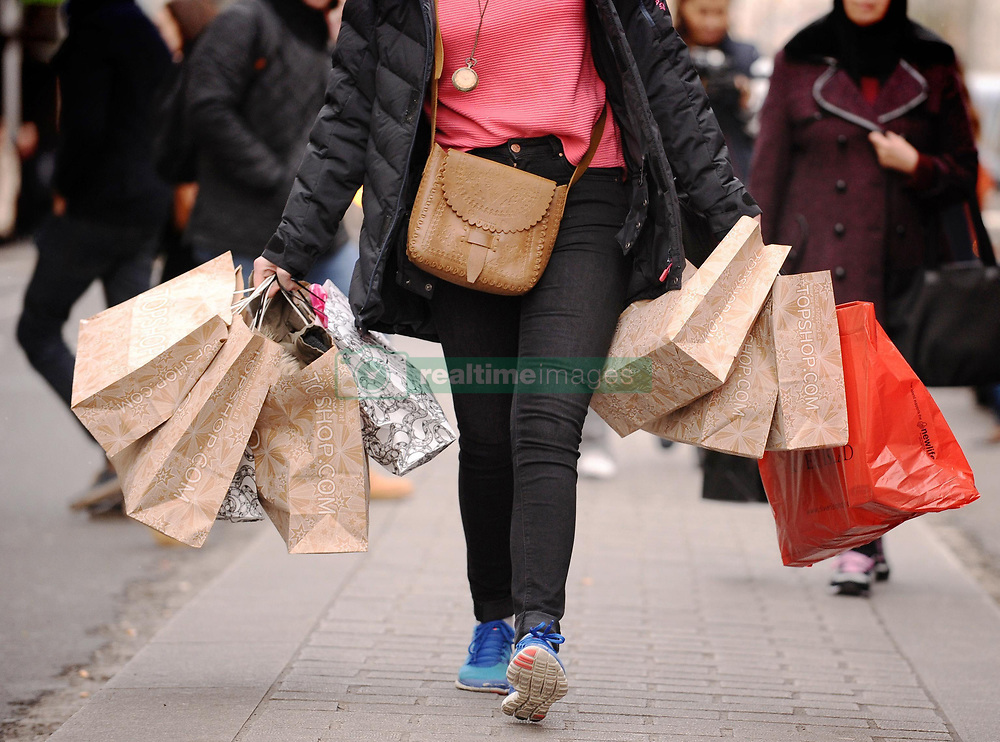 File photo dated 06/12/11 of a lady carrying shopping bags. Retail sales sunk last month and online trading hit record lows as shoppers tightened their belts in the face of rising inflation, new figures have shown.