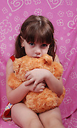 frightened Girl of 5 in red dress hugs her teddybear for support and protection
