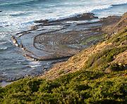 Intensely folded rock of wave cut platform.  Rocky rugged coastal landscape on the Rota Vicentina Fisherman's Trail long distance footpath route, near Bunheira, Aljezur, Algarve, Portugal, Southern Europe