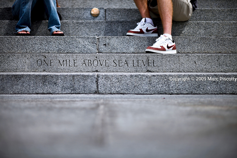 """SHOT 8/13/09 2:04:39 PM - The words """"One mile above sea level"""" mark the spot orginally thought to be 5,280 feet (or one mile) above sea level on the steps of the Colorado State Capitol. The official elevation of Denver is measured outside the west entrance to the building, where the fifteenth step is engraved with the words """"One Mile Above Sea Level."""" From this step, around dusk, a magnificent view of the sun setting behind the Rocky Mountains can be taken-in at 5,280 feet (1,609 m). A second mile high marker was set in the 18th step in 1969 when Colorado State University students resurveyed the elevation. Finally, in 2003, an even more accurate measurement was made with modern means and the 13th step was identified as being one mile (1.6 km) high where a 3rd marker was installed. Colfax Avenue is the main street that runs east and west through the Denver-Aurora metropolitan area in Colorado. As U.S. Highway 40, it was one of two principal highways serving Denver before the Interstate Highway System was constructed. In the local street system, it lies 15 blocks north of the zero point (Ellsworth Avenue, one block south of 1st Avenue). For that reason it would normally be known as """"15th Avenue"""" but the street was named for the 19th-century politician Schuyler Colfax. On the east it passes through the city of Aurora, then Denver, and on the west, through Lakewood and the southern part of Golden. Colloquially, the arterial is referred to simply as """"Colfax"""", a name that has become associated with prostitution, crime, and a dense concentration of liquor stores and inexpensive bars. Playboy magazine once called Colfax """"the longest, wickedest street in America."""" However, such activities are actually isolated to short stretches of the 26-mile (42 km) length of the street. Periodically, Colfax undergoes redevelopment by the municipalities along its course that bring in new housing, trendy businesses and restaurants. Some say that these new developments detract from the chara"""