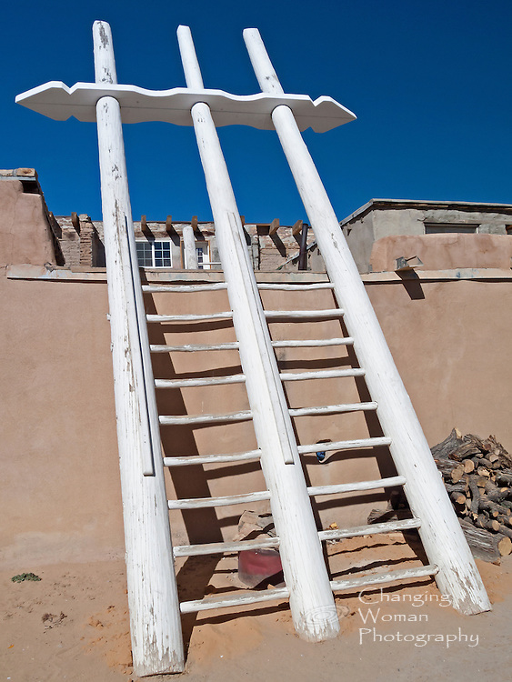 Acoma people built multi-story houses that included a sacred space, or kiva, on the ground floor. When Spanish conquerors attempted to eradicate Puebloan religious beliefs and practices, kivas were hidden behind high walls or transformed into windowless rooms accessible only by ladder.  Straight pine logs used to build ladders had to be hauled from the forested slopes of Mt. Taylor, many miles away.  This ladder's worn rungs, along with a family's firewood piled nearby, testify to its continued use.