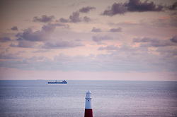 Looking out to sea as a ship passes Portland Bill Lighthouse, Isle of Portland, Dorset, England, UK.