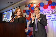 Garden City, New York, USA. November 6, 2018. Nassau County Democrats watch Election Day results at Garden City Hotel, Long Island. Congresswoman KATHLEEN RICE speaks at podium, after winning re-election as New York's Representative for Fourth Congressional District. JAY JACOBS, Chairman of Nassau County Democratic Committee, introduced Rice.