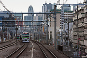 Commuter trains in front of the Shinjuku skyline with the Cocoon Tower in the centre, Tokyo, Japan. Friday March 11th 2011