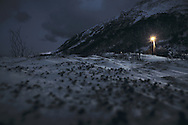 A single street light illuminates the snowy ground on a dark winter night in Bergsfjord, Finnmark, Norway
