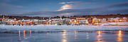 The Kennebec River is chock full of ice and snow covers the rooftops in this winter scene from across the river. The heart of downtown can be seen under the light of the setting moon.