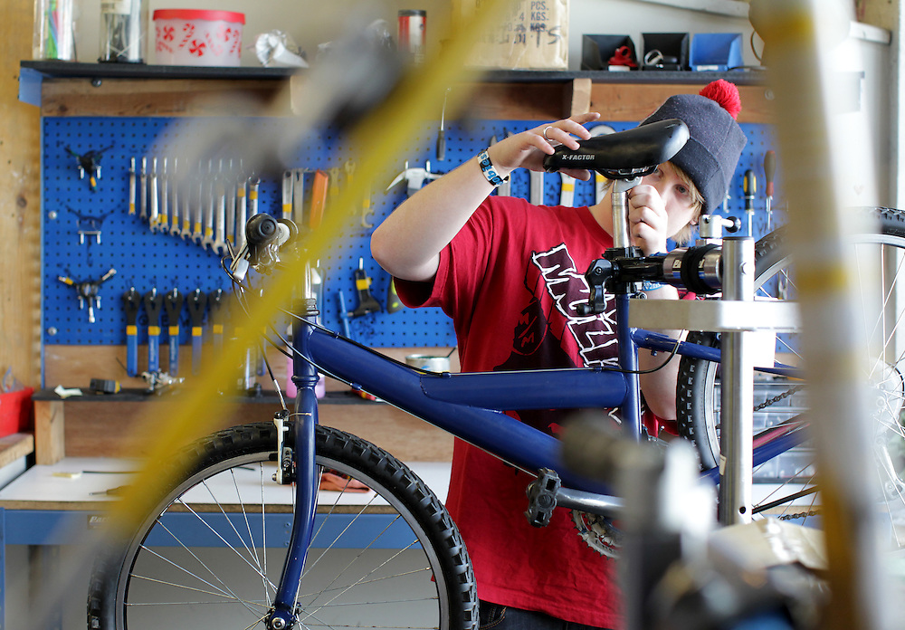 Ty Spangle, 17, adjusts a seat on a refurbished bicycle at Express Bike Shop in St. Paul, Minnesota.  Formerly a Youth Express apprentice, Spangle is now a mechanic at the shop, teaching skills to new youth in the program..