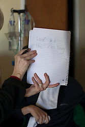 Judy Cox writes phrases for her son Chris, 29, a traumatic brain injury survivor, to do the corresponding action, which he completed almost every time, Destin, Fla., Nov. 18, 2011. Judy and her husband Wayne take care of their son, who was left with debilitating back pain after an A.T.V. accident. Cox underwent physical therapy to no avail and accidentally overdosed on Oxycontin, leaving him clinically deceased for 15 to 30 minutes. He was revived but suffered severe lack of oxygen to his brain and was diagnosed as minimally conscious. Cox's family entered him into a clinical trial, testing medicines that evoked Òparadoxical excitation,Ó such as Ambien, and have witnessed a heightened sense of awareness in their son.