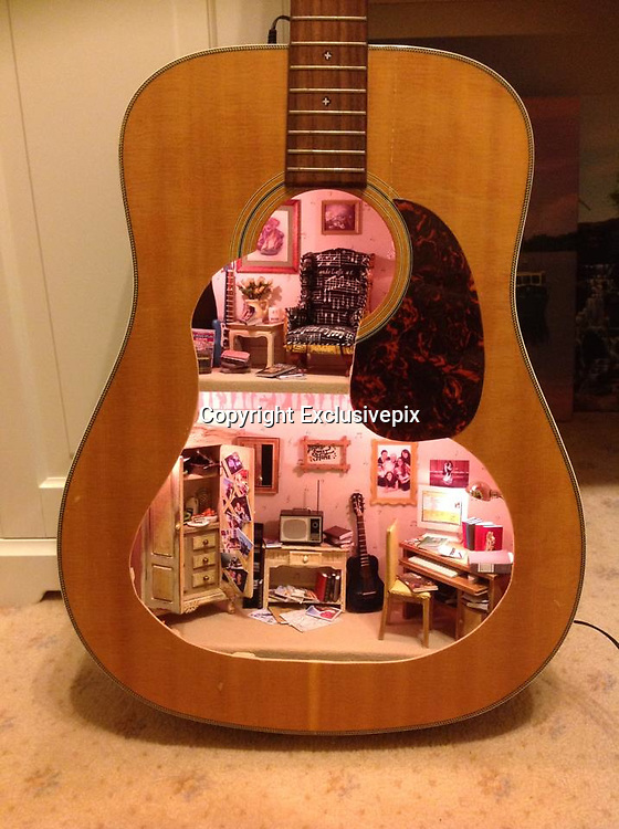 Talk about the home of music: Resourceful mum carves doll's house INSIDE a guitar as a gift for her daughter<br /> <br /> This room should have the perfect acoustics.<br /> Miniatures artist Lorraine Robinson, originally from Mansfield, carved a doll's house into a guitar using incredible attention to detail.<br /> The 49-year-old, who now lives in Australia, used her own prized instrument for the intricate project, as a special present for her daughter Cathryn.<br /> 'I couldn't see her keeping a plain old room box, and wanted it to be unusual,' said Ms Robinson.<br /> 'So I thought of many ideas that would incorporate her passions.<br /> 'I wanted to give her a gift that she would cherish and would be specific to her.<br /> 'This guitar was my first guitar and I knew she would recognise it because of the stress fracture that runs down the top of the body on the front left-hand side.<br /> <br /> 'Cathryn spotted this straight away and hugged me even more knowing full well what I had done.'<br /> The two-floor room has exquisite detailing with tiny pencils visible on a table along with cupboards, stairs and other furniture.<br /> Ms Robinson spent about two weeks on the guitar dwelling, working between eight and 10 hours a day.