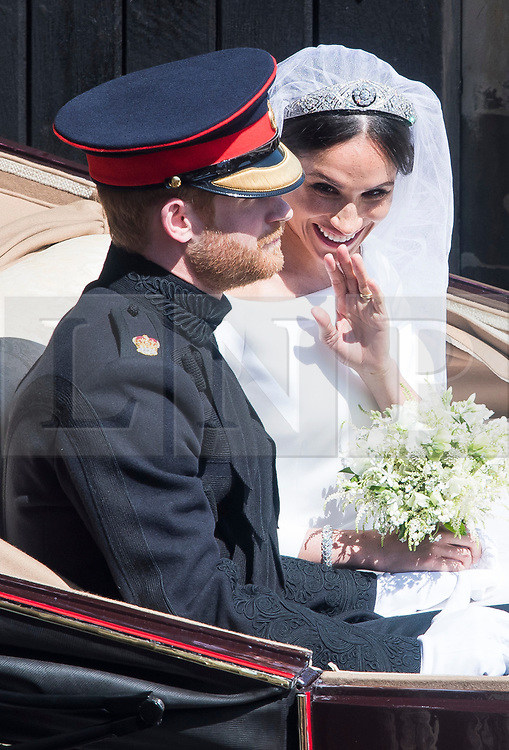 © Licensed to London News Pictures. 19/05/2018. London, UK. An open top carriage carrying Prince Harry and Meghan Markles leaves the chapel to make its way through Windsor. Guests arrive at The wedding of Prince Harry, The Duke of Sussex to Meghan Markle, The Duchess of Sussex, at St George's Chapel in Windsor. Photo credit: Ben Cawthra/LNP