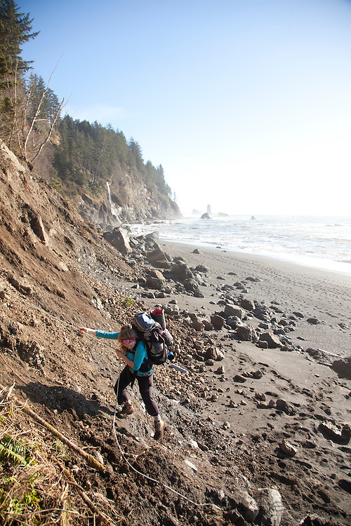 Young woman using a rope to climb a muddy bank after rain caused a landslide while backpacking near Third Beach in Olympic National Park, WA.