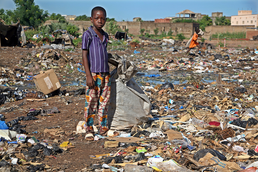A young boy scavenges through a waste dump looking for anything plastic that he can sell for recycling, Bamako, Mali.