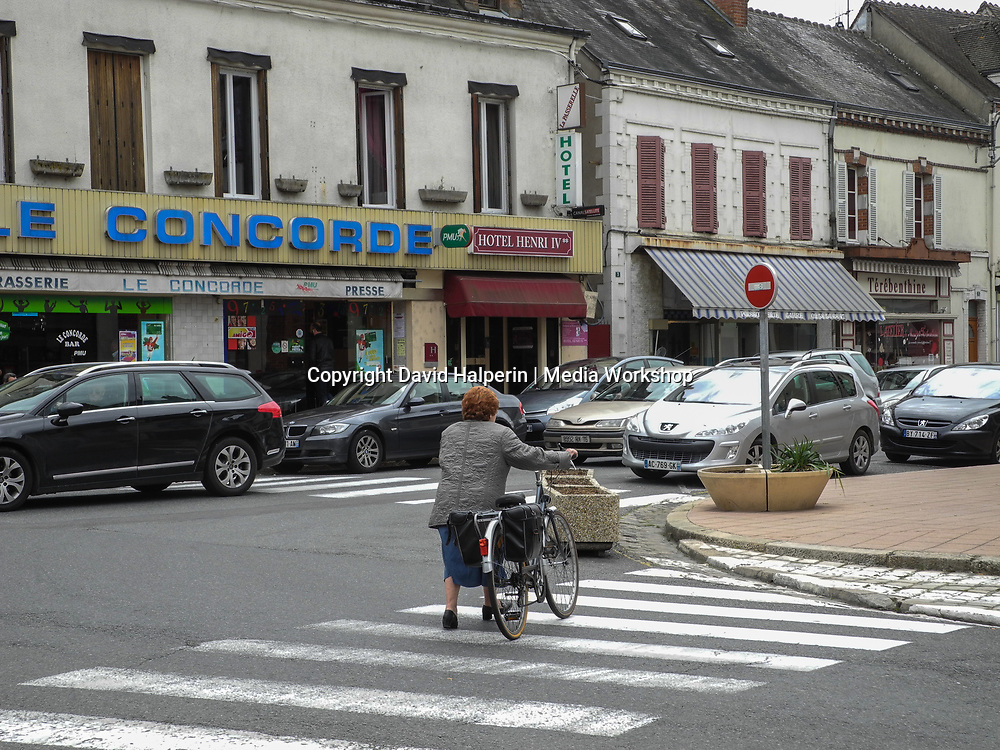 Street scene,  woman with bicycle, Sully-sur-Loire