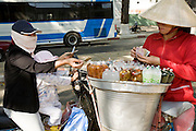 "09 MARCH 2006 - HOP CHI MINH CITY, VIETAM: A woman and her child on a motorscooter buy refreshments from a woman on a bicycle in Ho Chi Minh City (Saigon), Vietnam. Many Vietnames eat ""on the run,"" buying food from street vendors. People in HCMC frequently wear face masks because of pollution in the city.   PHOTO BY JACK KURTZ"