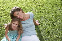 Portrait of mother and daughter (5-6) sitting on lawn