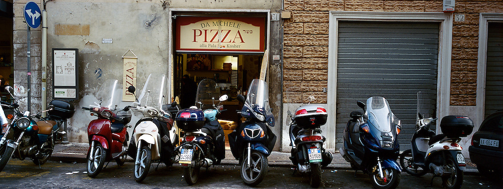 A line of scooters parked in front of a pizzeria in Rome, Italy. 23rd July 2011. Photo Tim Clayton
