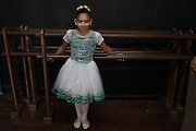 A girl waits before the start of her ballet class at the 'Ballet Santa Teresa' academy in Rio de Janeiro August 15, 2012. 'Ballet Santa Teresa', a non-governmental organization (NGO) gives children who live in areas with social risk, some suffering domestic violence, free ballet classes and other activities as a part of socio-cultural integration project. Photo by: Pilar Olivares