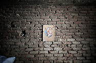 Egypt, Cairo: A religious sign depicting the Virgin Mary is hanged on a wall inside a factory in   Moqattam, the christian coptic quarter in Cairo where live 40.000 Zabbaleen (garbage collectors). ph.Christian Minelli.