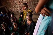Sundar (center, in black), 8-9 years, sits amongst other rag-picker's children in class in the Nai Duniya activity center in remote Lodha Basti, Manana village, Samalkha town, Haryana, India on 15th June 2012. Sundar walks 1.5km to and from her rag-picking work each day. Most of these children are rag-pickers themselves. They are now able to go to school from 8-12 in the morning, and study again at the activity center after work at 4pm. A new program to encourage the rag-picker's children to attend school is underway, to keep them from becoming the next generation of rag-pickers in cities. Photo by Suzanne Lee for The National
