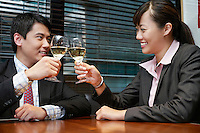 Two business people toasting with wine glasses sitting in cafe