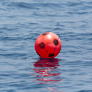 Discarded plastic toy ball floating in the middle of the ocean. Even innocent toys can become plastic waste that poisons the oceans.