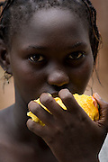 A girl eats a mango near the Essaout primary school in the village of Essaout, Senegal, on Thursday June 14, 2007...