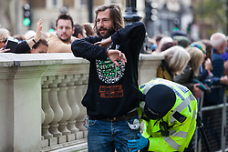 London, UK. 9 October, 2019. Police officers arrest a climate activist from Extinction Rebellion who had locked himself to another activist using an arm tube to block Whitehall on the third day of International Rebellion protests.