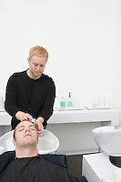 Male client has hair shampooed in unisex hair salon