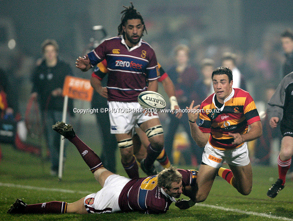Richard Kahui (Waikato) gets his pass away as Jimmy Cowan (Southland) tackles him during the Air New Zealand Cup rugby match between Southland and Waikato at Rugby Park Stadium, Invercargill, on Saturday 5 August 2006. Photo: Richard Jones/PHOTOSPORT<br /> <br /> <br /> 050806 week 2 npc