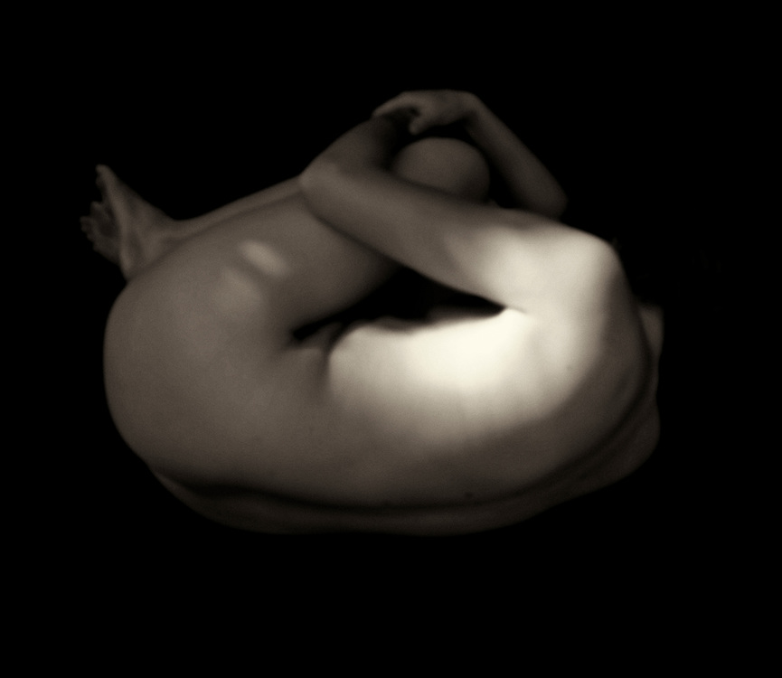 This nude female figure surrounded by darkness has her back to us. Was it something we said? Something we did? Is it possible that we are simply intruding on the despair this woman apparently feels? There is even the possibility that she isn't despairing at all. Whether you believe that we are merely projecting our feelings onto a woman with her own, unknown narrative, or if you have clear answers to the questions above, there is something to this nude figure study that simply captivates you. This is a figure study that stays with you. Available exclusively as wall art. .<br />
