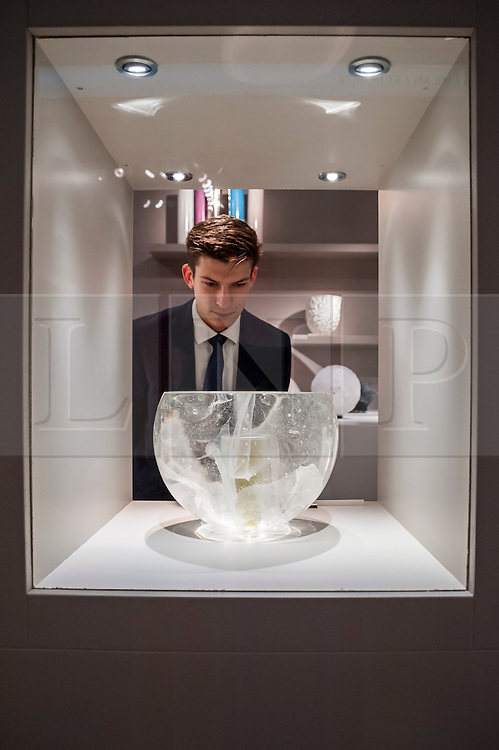 © Licensed to London News Pictures. 24/06/2015. London, UK.   A gallery owner inspects an ornate glass vase at the preview of Masterpiece London, the international cross-collecting Fair for art, antiques and design which takes place at The Royal Hospital Chelsea 25 June to 1 July. Photo credit : Stephen Chung/LNP