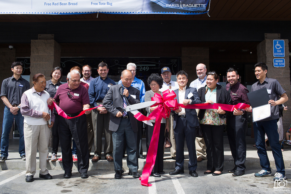 Mayor Jose Esteves, Paris Baguette Cafe staff, and members of the Milpitas Chamber of Commerce cut the ribbon with oversized scissors during the Grand Opening Ribbon Cutting Ceremony at Paris Baguette Cafe in Milpitas, California, on May 16, 2014. (Stan Olszewski/SOSKIphoto)
