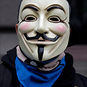 Close up of masked &quot;Anonymous&quot; protester, at the &quot;Occupy Wall Street&quot;  protest  on September 17, 2011.<br /> <br /> Anonymous is a group initiating active civil disobedience and spread through the Internet while staying hidden, representing the concept of many online community users simultaneously existing as an anarchic, digitized global brain. <br /> <br /> It is also generally considered to be a blanket term for members of certain Internet subcultures, a way to refer to the actions of people in an environment where their actual identities are not known.